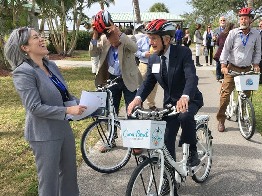Courtney Reynolds, program manager of Florida Department of Transportation's reThink Your Commute program, jokes with Cape Canaveral City Council member Rocky Randels at Manatee Sanctuary Park in Cape Canaveral, where a new bike-share program debuted.