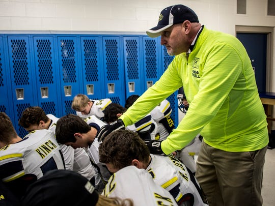 Algonac coach Scott Barnhart stands with the team as they pray in the locker room during a Division 5 semifinal football game Saturday, Nov. 19, 2016 at Harper Creek High School in Battle Creek.