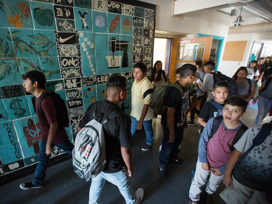 Students at the new campus of  La Academia Dolores Huerta walk to class past a mural left behind by the previous school the Mesilla Valley Leadership Academy  which occupied the building before La Academia moved in. Thursday August 16, 2018. The move to the Mesilla Park location offers the 130 students more classroom space as well as a specific lunch area and basketball court which the old campus did not have.