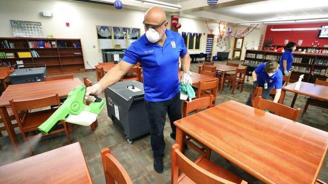 Custodial workers from Orange County Public Schools in Orlando use electrostatic disinfectant sprayers to deep clean at Wetherbee Elementary School, Wednesday, March 18.