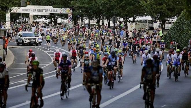 Riders leave the starting line during the 11th Pelotonia at North Bank Park in the Arena District in Columbus on Aug. 3, 2019. This year's traditional Pelotonia bicycling was canceled because of the COVID-19 coronavirus pandemic and replaced with a virtual event.