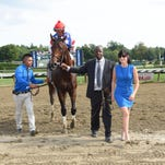 Trainer Maria Borell, groom Cordell Anderson and exercise rider Omar Torres lead in Runhappy after the colt captured Saratoga's Grade I King's Bishop.
