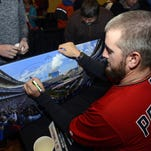 The Minnesota Twins' Glen Perkins signs an autograph during the team's TwinsFest on Friday in Minneapolis.