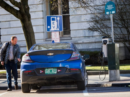 Doug Merrill of Shelburne approaches his electric-hybrid Chevy Volt on Wednesday at a charging station at Church and Main streets in Burlington.