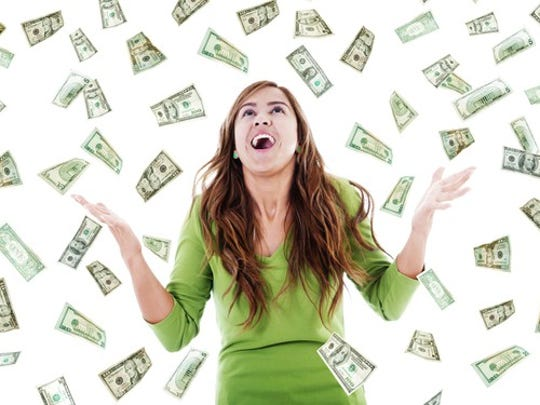 Young woman surrounded by cash falling from above.