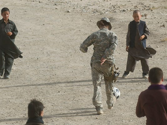 Vermont National Guard soldier Sgt. Chrissy Nisun of Lincoln plays soccer with Afghan kids. (RYAN MERCER, Free Press)