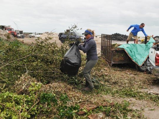 Celeste Anderson of Green Source Group in Cape Canaveral empties a truck bed full of yard waste. Trucks and other vehicles formed lines outside along Sarno Road, and filled the top of the hill to unload tons of yard debris from Hurricane Matthew, at Brevard County's solid waste facility off Sarno Road in Melbourne.