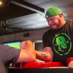 Brandon Morris arm wrestles Ray Hennerichs, left, of Denham Springs, La., in a super match at the WAL Qualifier at Sidelines Sports Bar and Grill in Fort Myers on Saturday, April 18, 2015.