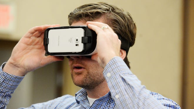 Cody Ulven, Director of Sales & Marketing at the Ramkota tries out a Samsung Gear VR headset, Feb 4, 2016. One of the many uses for the headset could be to show prospective customers a 3-D interactive view of a meeting or event space in the hotel.