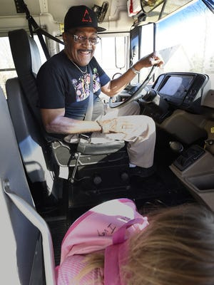 Elise Ivey, 4, gets a cheerful goodbye from bus driver Joe Thompson as she leaves his school bus.