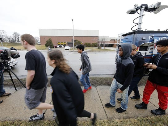 Young people walk  past members of the media and  West