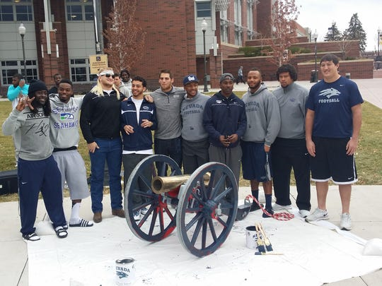 Nevada Wolf Pack seniors with Fremont Cannon on Sunday after they painted it blue