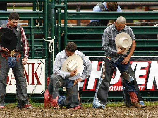 Bull riders bow their heads in prayer.