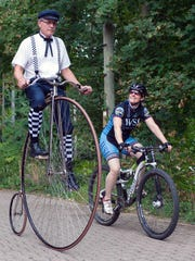 Dan Johnson, on his penny-farthing bike, rides alongside Angela Bowers on her modern Cannondale mountain bike.