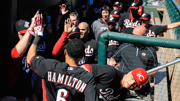 Billy Hamilton is greeted in the dugout by teammates during a spring training game.