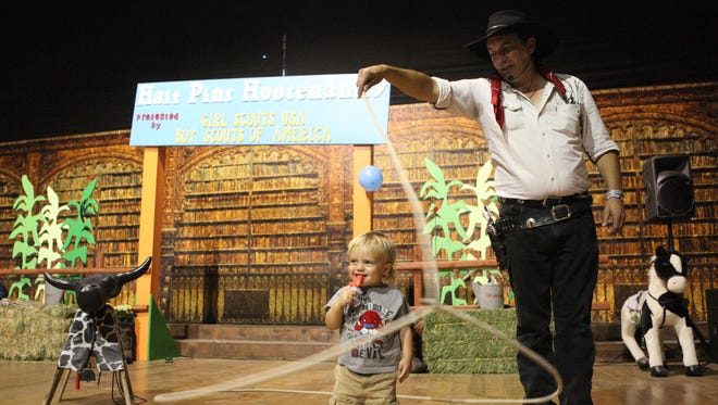 """Lakewood resident Parker Thielemann, 1, stands still as John """"Johnny Hot Shot"""" Mincks lassos around him at the Half Pint Hootenanny during Stagecoach on Friday, April 25, 2014 in Indio, Calif."""