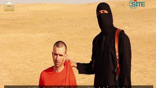 Image released by SITE Intelligence Group on September 2 shows footage of a masked militant threatening to kill British David Cawthorne Haines.