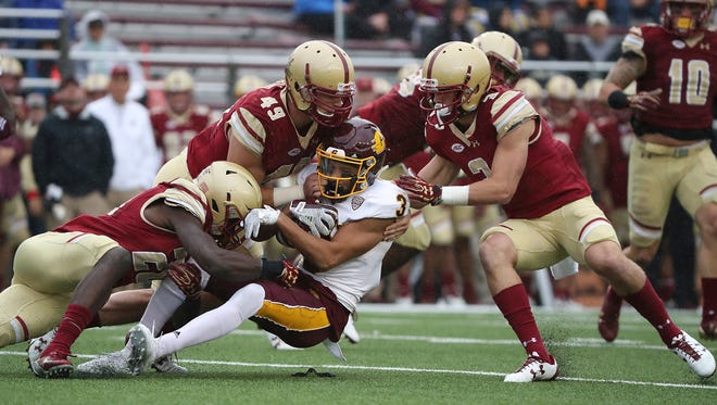 Boston College defenders, from left,Lukas Denis, Kevin Bletzer and Michael Walker team up to gang tackle Central Michigan Chippewas Mark Chapman during the second half of an NCAA college football game at Alumni Stadium Saturday, Sept. 30, 2017, in Boston. (Matthew J. Lee/The Boston Globe via AP)