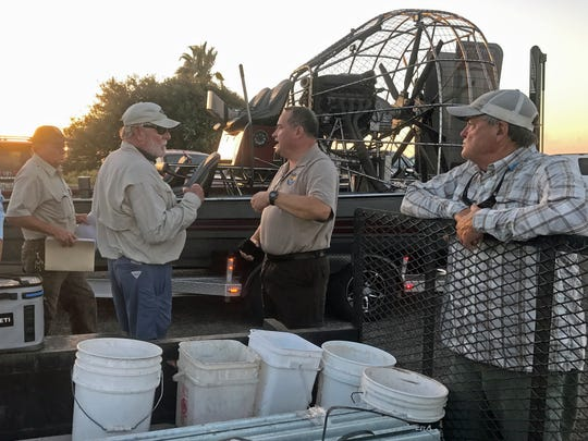 FlatsWorthy founder Chuck Naiser (left) talks with Joe Saenz, superintendent of the Aransas National Wildlife Refuge at Goose Island State Park, before crews set  out to post signs at the refuge.