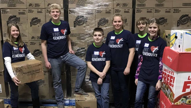 Eighth-grade students at Martin Luther Elementary School, including Elizabeth Oakland, Judah Kolell, Connor Romberg, Kate Henze, Max Farah and Olivia Race, were among those who spent three hours at the Feeding America Warehouse sorting, lifting, wrapping and stocking 5,788 pounds of donated food.