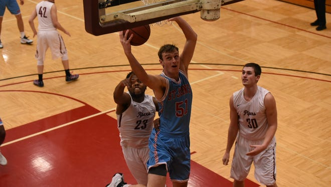 Tyler Weiss of St. John's goes up for a layup as Hamline's Kalu Abosi (23) and Isaac Brooks (30) look on during MIAC action Wednesday night at Hutton Arena in St. Paul.