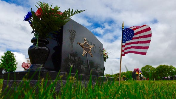 A flag waves at a veteran's grave at the St. Joseph