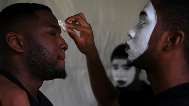 The Men of Valor are a mime ministry that express their faith through dancing. Before taking the stage, (right) Dean Bennett puts makeup on his brother Michael Bennett as their brother Joseph Bennett looks on during Jamaica Day at Eastside Park in Paterson on Aug. 6.