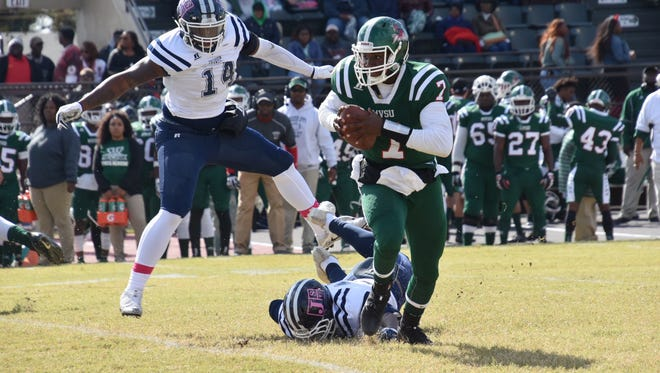 Mississippi Valley quarterback Dwayne Betts runs away from Jackson State linemen Keontre Anderson (14) and Khalil Johnson Saturday in Itta Bena.