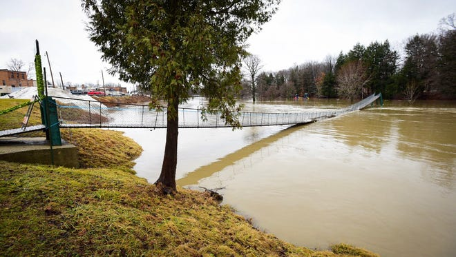 The Black River submerges a portion of the Croswell Swinging Bridge Wednesday following warm temperatures and heavy rains.