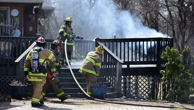 Firefighters extinguish a deck fire in Port Huron Township Monday afternoon.