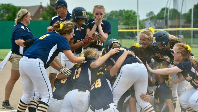 Hartland falls into a pile as it celebrates a walk-off, RBI single by Delanie Grundman in the seventh inning in a 3-2 win over Clarkston in a MHSAA softball quarterfinal at Wayne State University on Tuesday.