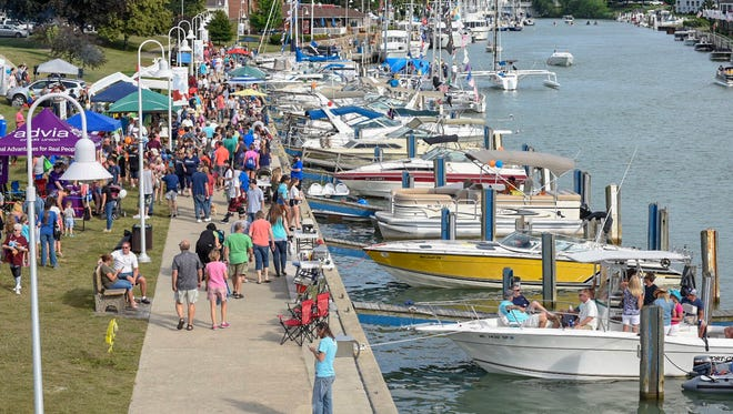 People walk through River Street Marina near 10th Street on Family Night Thursday, July 12, 2018, during Boat Week in Port Huron.