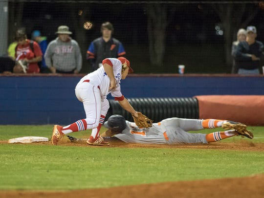Third baseman Izzy Ham (8) tags out  Jacob Burke (13) as he dives into third during the Escambia vs Pace high school baseball game at Pace High School on Friday, April 7, 2017.
