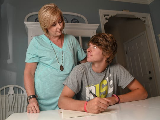Camden Bratcher, right, a rising senior at Belton-Honea Path High School, sits with a thank you card he plans on sending to the doctor who helped him. His mother Donna, left, needed to find another hospital when recently was not given treatment from his own family doctor office because he had not been in the office for care in a while.