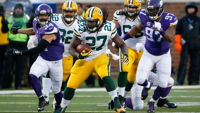 Green Bay Packers running back Eddie Lacy (27) runs past Minnesota Vikings strong safety Andrew Sendejo (34) an defensive end Everson Griffen (97) during the first half of an NFL football game in Minneapolis, Sunday, Nov. 22, 2015. (AP Photo/Ann Heisenfelt)