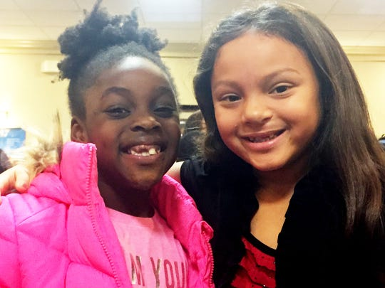 Elaina Yates, right, shared her experience of overcoming a cleft lip and missing thumb at a New Year's prayer. Elaina is 9.