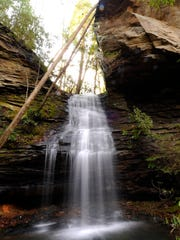 A waterfall streams over sheets of shale along the