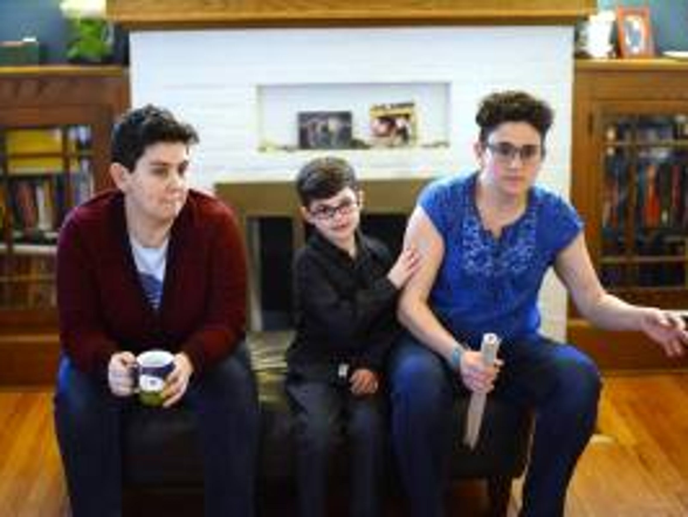 Avner Valentine, 7, with parents, Mary Valentine, left,