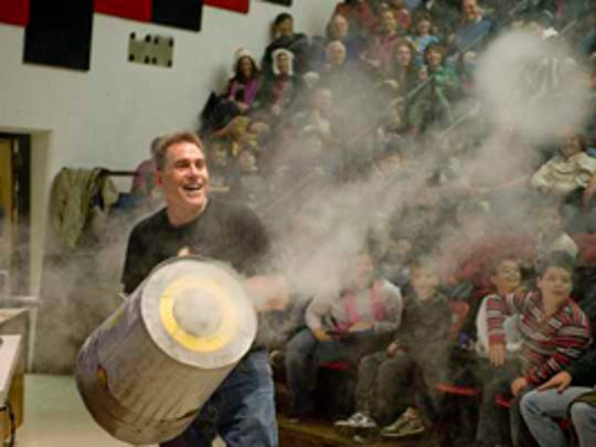 Physics Support Specialist David Maiullo demonstrates a device made from a garbage can that produces large smoke rings