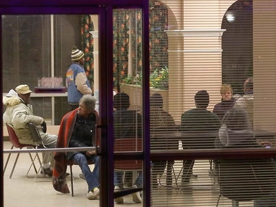 Residents of the Windsor Apartments wait in the lobby after a fire on the 12th floor of the high-rise Tuesday night in Wilmington.