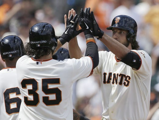 San Francisco Giants' Madison Bumgarner, right, is congratulated by Brandon Crawford (35) after Bumgarner hit a grand slam off Arizona Diamondbacks' Matt Stites in the sixth inning of a baseball game Sunday, July 13, 2014, in San Francisco.