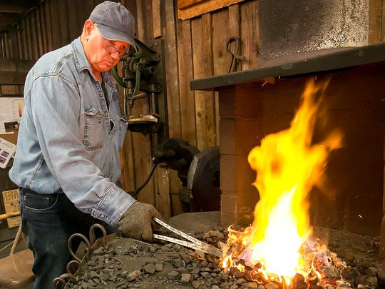 Clyde Cross heats a piece of metal as blacksmiths showed their work at Murfreesboro Parks and Recreation's Harvest Days at Cannonsburgh Village.