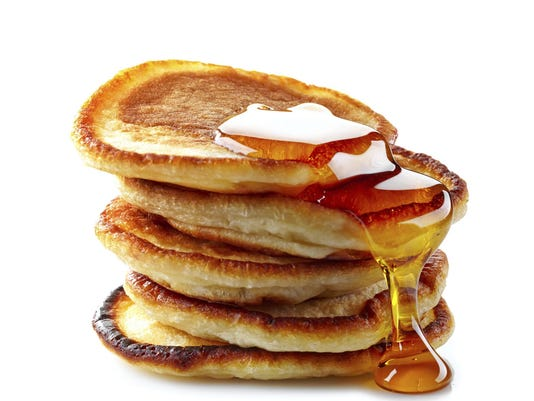 Stack of pancakes dripping with maple syrup
