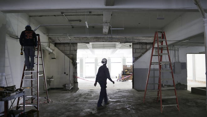 Electricians for Motor City Electric Co. Jason Hagemeister, left, and Dakari Shaver, help wire the location of what will be Carhartt's first major retail store in Michigan. The store is located in the Midtown area on Cass Avenue in Detroit and is projected to open in late summer.