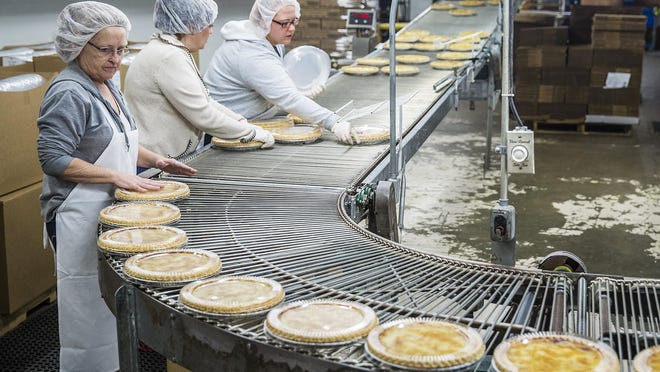 Pies are packaged by workers as they move along a conveyer belt at Wick's Pies.