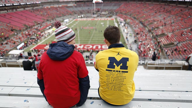 Brothers Stephen Fedak, a Michigan graduate, and Andrew Fedak, an Ohio State student, both of Livonia, Mich., take their seats prior to The Game on Nov. 24, 2018. The matchup has been scheduled as both teams' regular-season finale in nearly every season since 1935, but this season it could be played in the warmth of September.