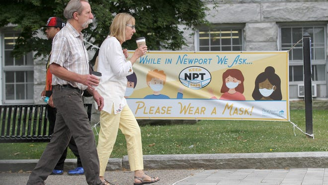 Maskless pedestrians walk past a banner outside Newport City Hall reminding people to wear masks.