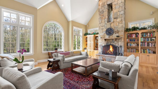 The family room features a floor to ceiling sandstone fireplace with keyhole window surrounded by built-in bookcases. French doors in the room lead to a bright sunroom with tiled floor and a wall of glass that offers scenic views of the grounds.