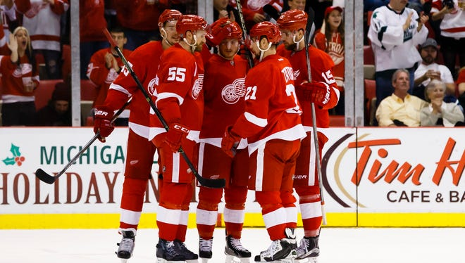 The Red Wings celebrate a goal by center Riley Sheahan (right) in the second period of the Wings' 4-2 win over the Flames Sunday at Joe Louis Arena.