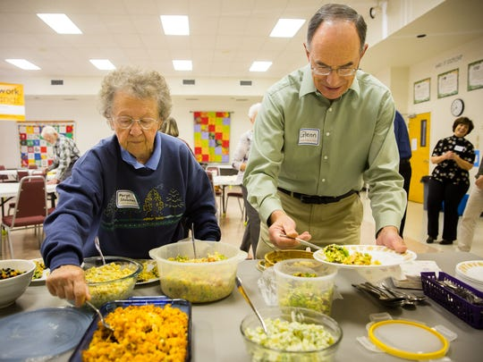 Marge Shouman and Glenn Kuehn load up their plates at Trinity Lutheran Church's monthly Ladies for Luther potluck lunch.
